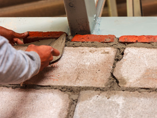 stock-photo-worker-installing-red-brick-with-trowel-for-wall-of-room-in-house-148238252